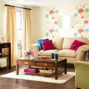 a bright floral wall, colorful furniture and pillows bring a strong summer feel to the space