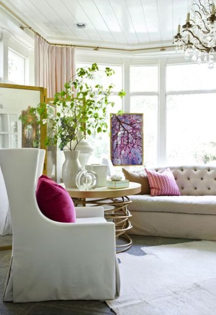 greenery branches, a floral artwork and bright pillows for infusing a neutral living room with color, prints and bring a summer feel