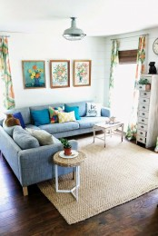 a neutral living room with a blue sofa, colorful pillows, bright printed curtains and a gallery wall for a summer feel