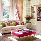 bold and floral print pillows and an ottoman, pink striped curtains and blooms for a summer living room