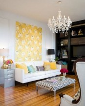bold pillows, a floral artwork, some blooms in vases for a bright feel in the living room