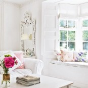 some printed pillows and bold blooms will easily turn your neutral living room into a bright summer one