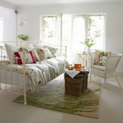 a chic vintage summer living room with floral rpint textiles, a green print rug and lots of greenery in pots and vases