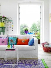 a bright and welcoming summer living room with bold floral pillows, with a colorful printed rug and some bold blooms in pots inside and outside, on the balcony