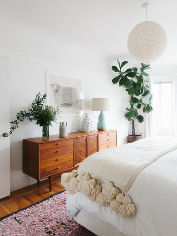 a welcoming boho meets mid century modern bedroom with boho rugs, a warm colored dresser and much potted greenery