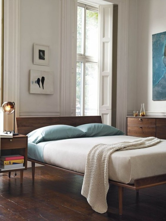 a mid-century modern bedroom with elegant rich stained wooden furniture, artworks and some aqua accents