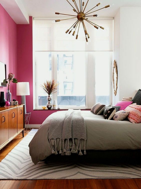 a bright and welcoming mid century modern bedroom with a fuchsia statement wall, a rich stained dresser and a brass burst chandelier