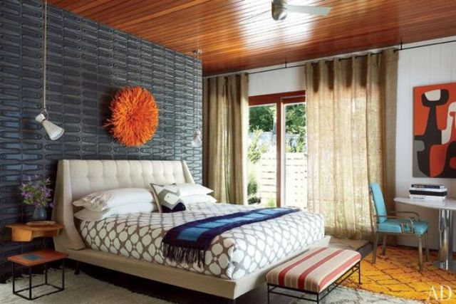 a colorful mid century modern bedroom with a grey metal wall, a neutral bed, a striped stool and a turquoise leather chair
