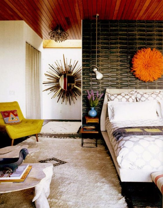 a bright mid-century modern bedroom with a cathcy black wall, a mustard chair, a fluffy rug and an orange decoration over the bed