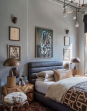 a chic and eclectic bedroom with a leather bed, matching artworks, a chic chandelier, wooden lamps and geometric nighstands plus a fur stool