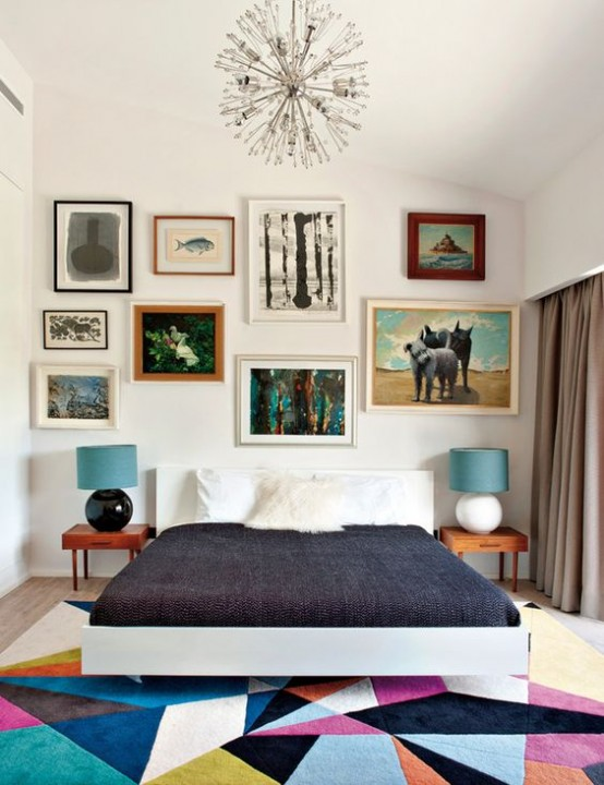 a colorful mid-century modern bedroom with a bright geometric rug, a bed, laconic nightstands and an eclectic gallery wall
