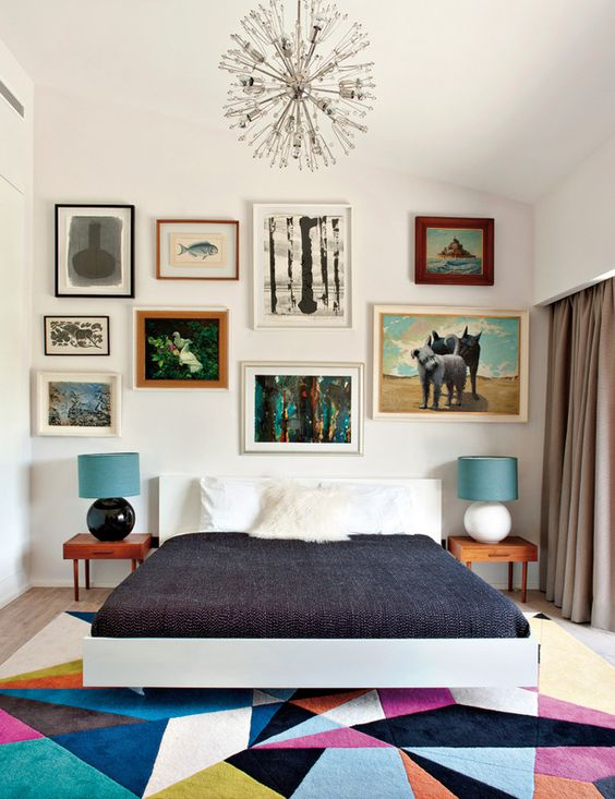 a colorful mid century modern bedroom with a bright geometric rug, a bed, laconic nightstands and an eclectic gallery wall