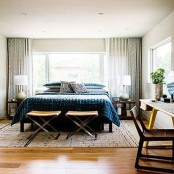 a stylish mid-century modern bedroom with a large bed, nighstands, desks and chairs plus much light