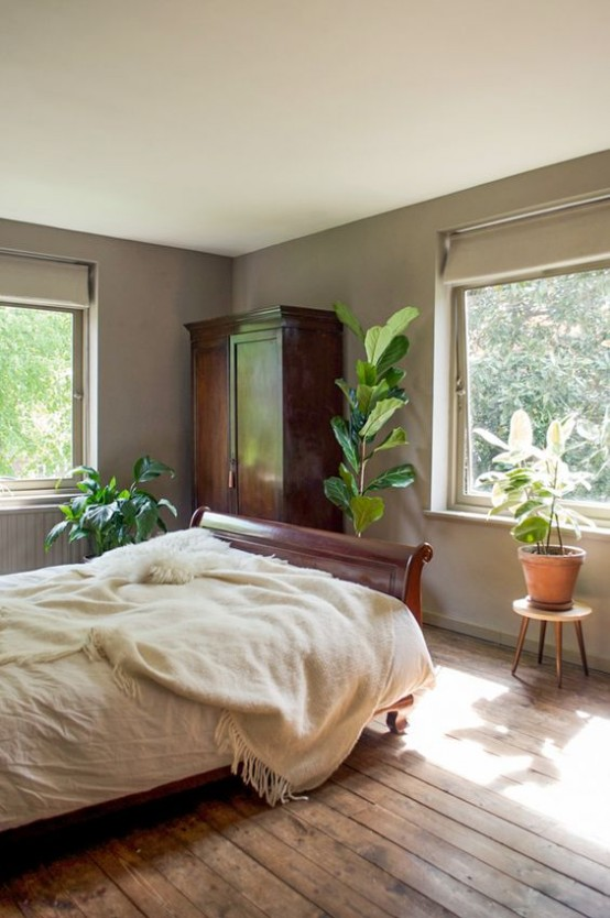 a mid-century modern meets boho bedroom with rich stained furniture, potted plants and shades