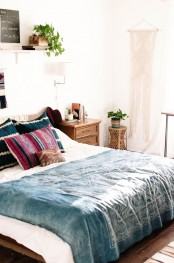 a boho meets mid-century modern bedroom with rich stained furniture, a macrame hanging and potted plants