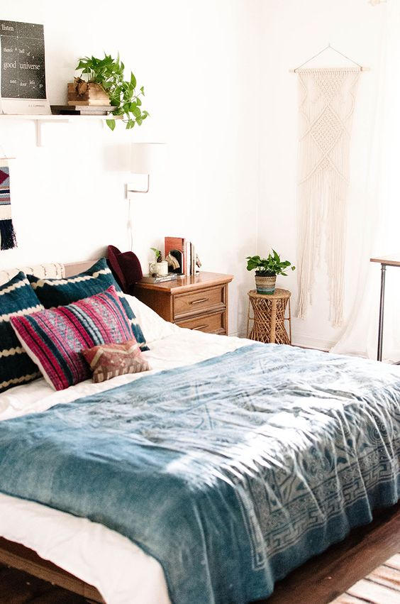 a boho meets mid century modern bedroom with rich stained furniture, a macrame hanging and potted plants