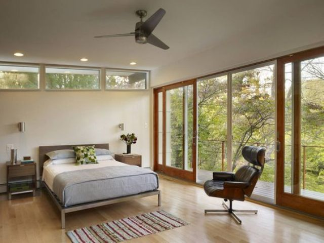 a mid century modern bedroom with a fully glazed wall, some small windows, a bed and a large comfy leather chair