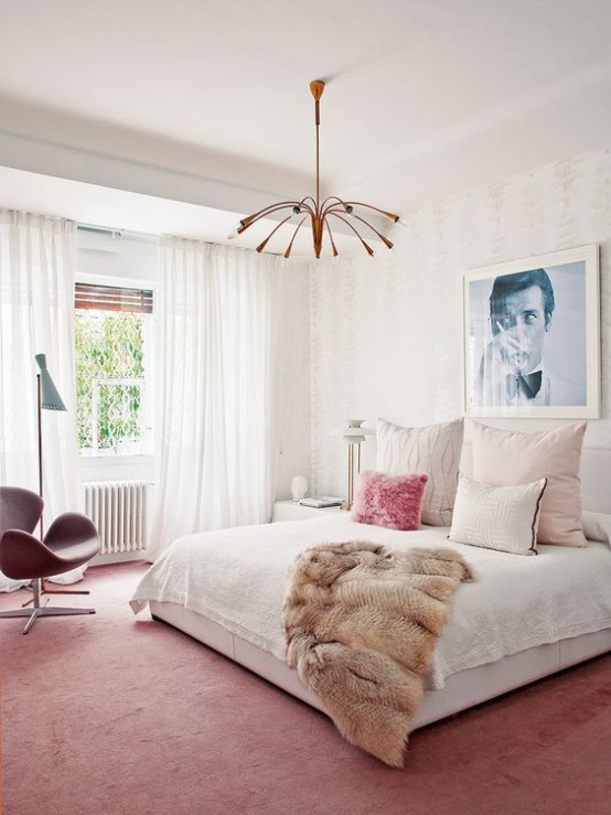 a bright mid-century modern bedroom with a pink rug and chair, a copper chandelier, a large bed and an artwork