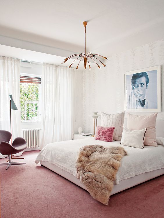 a bright mid century modern bedroom with a pink rug and chair, a copper chandelier, a large bed and an artwork