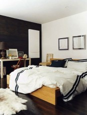 a monochromatic mid-century modern bedroom with a wooden bed and console plus a statement black wall
