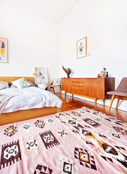 a welcoming and bright mid century modern space with warm stained wooden furniture, a pink rug and some artworks