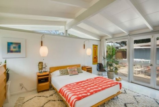 a bright mid-century modern bedroom with a warm colored bed and nightstands, rugs, artworks and windows for more light