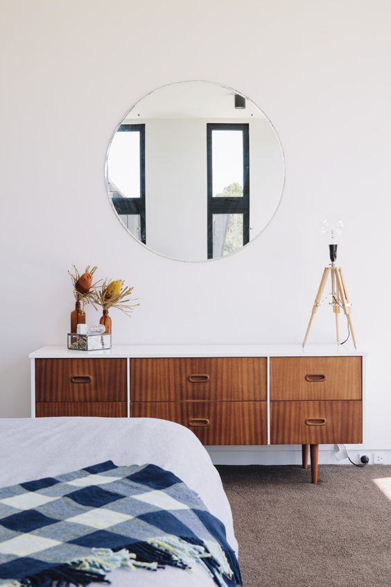 a stylish mid century modern bedroom with a wooden dresser, a round mirror, a large bed and a rug