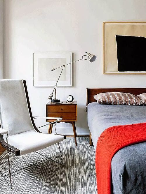 a laconic mid-century modern bedroom with a catchy thin chair, a cozy bed, a mid-century nightstand and a lamp