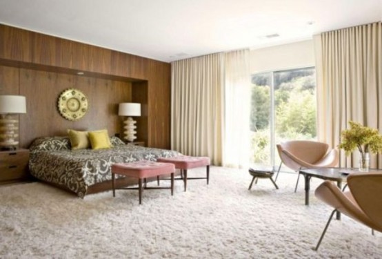 a mid-century modern bedroom with a fluffy carpet, a wood covered statement wall, leather chairs and pink stools