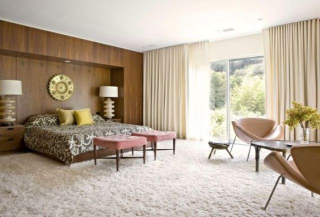 a mid century modern bedroom with a fluffy carpet, a wood covered statement wall, leather chairs and pink stools