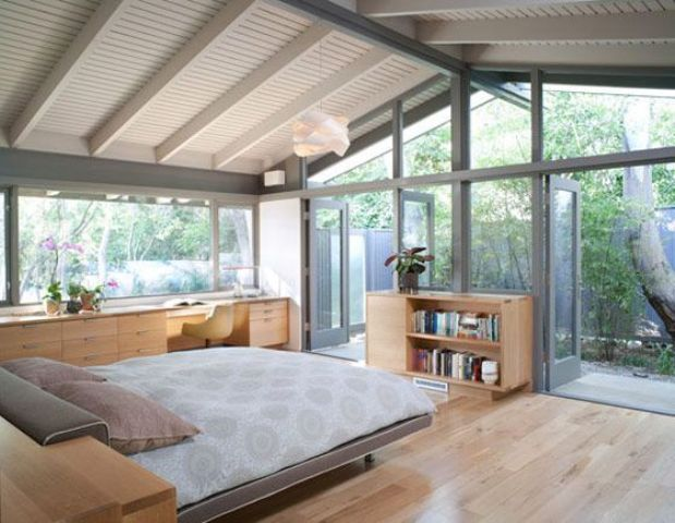 a cozy mid century modern bedroom done in neutrals, with glazed walls and a working space with a large desk
