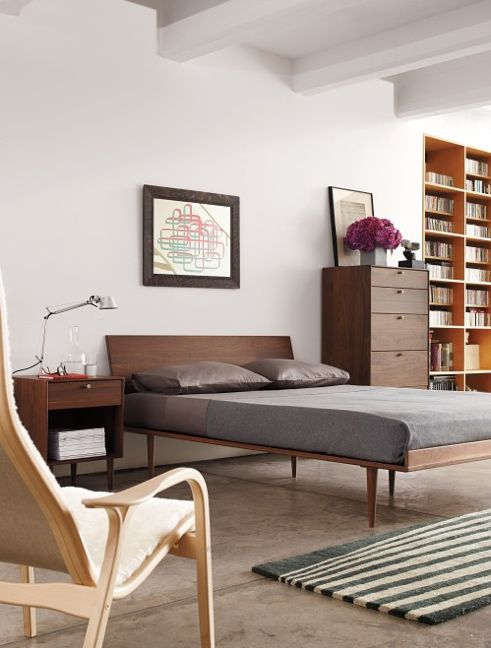 a mid-century modern bedroom with rich-stained furniture, striped rugs and artworks looks very fresh and light-filled