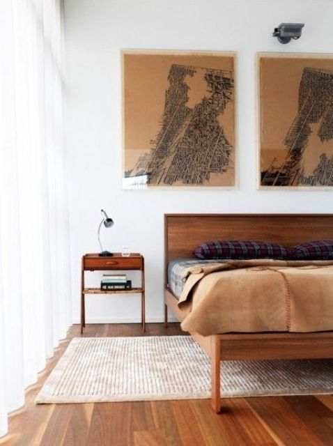 a chic mid century modern bedroom with rich stained furniture, artworks, a rug and moody bedding