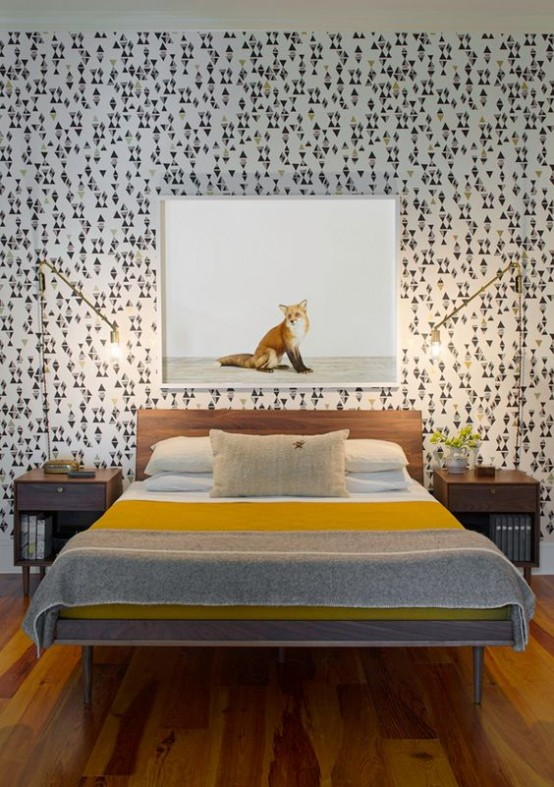 a catchy mid-century modern bedroom with geometric wallpaper, simple stained furniture and gilded table lamps