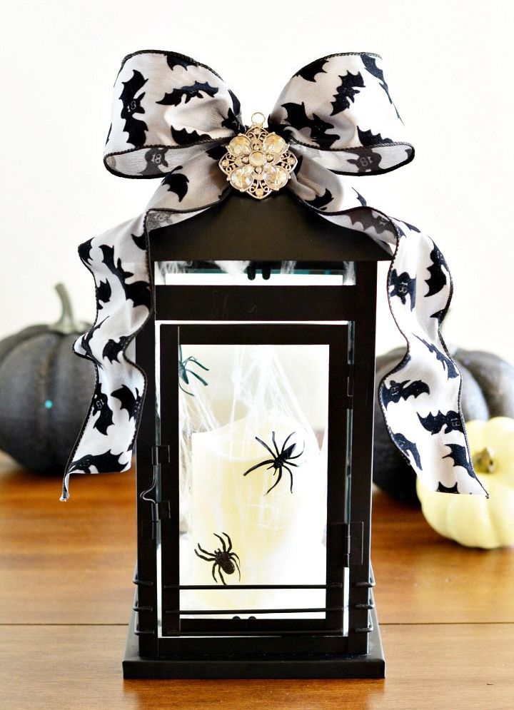 a candle lantern decorated for Halloween, with spiders inside and a bat printed ribbon bow on top