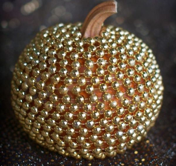 a pumpkin covered with gold beads is a chic and glam decoration you may rock at Halloween