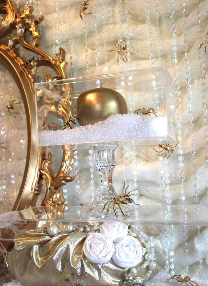 a crystal stand with a clear box and a gold apple, gold spiders and white fabric flowers for a glam Halloween party