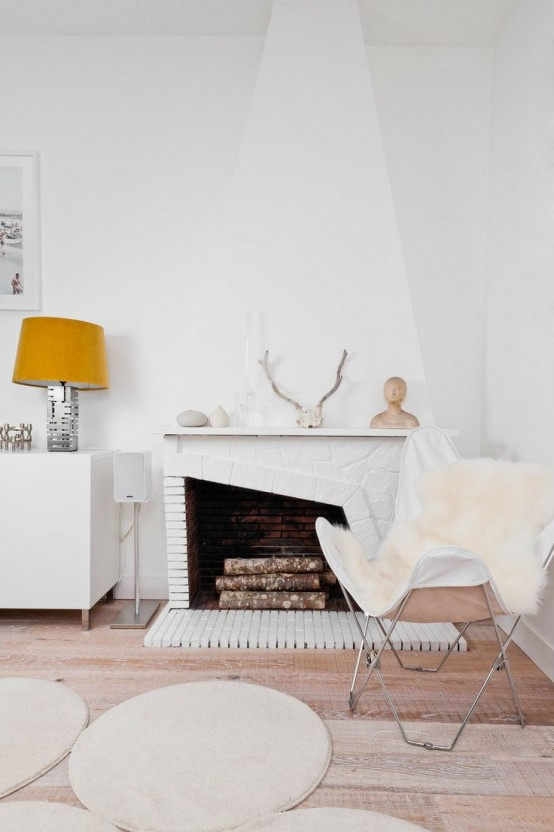 white faux fur covers and rugs, antlers, pebbles and firewood make this space Nordic yet fall-like