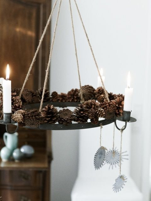 a creative pendant chandelier with pinecones and candles plus some paper decorations hanging down for a natural feel