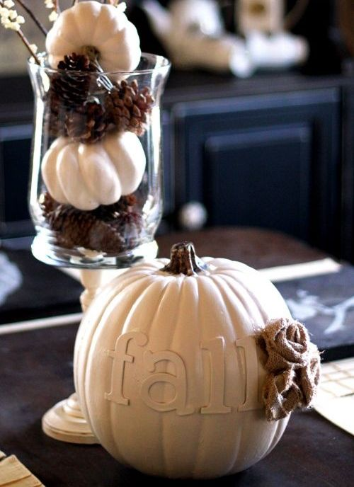 a Nordic fall centerpiece of a fake pumpkin with letters and a burlap flower and a vase with pinecones and mini pumpkins