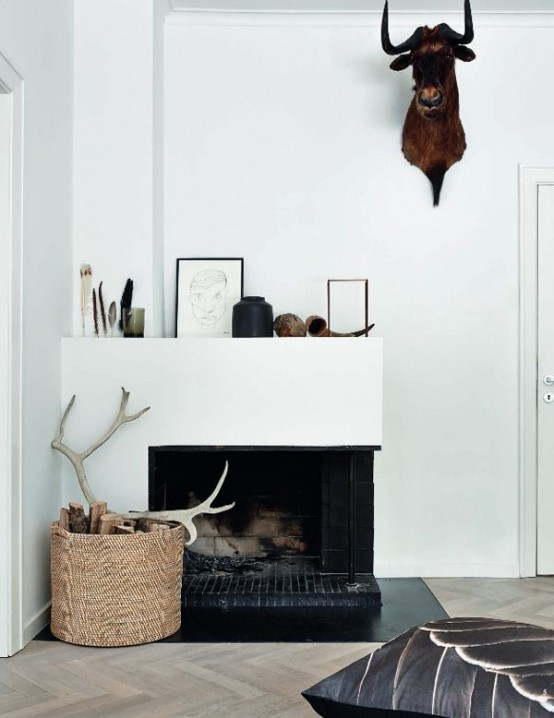 a basket with firewood and antlers plus a faux animal head on the wall for simple and modern fall decor