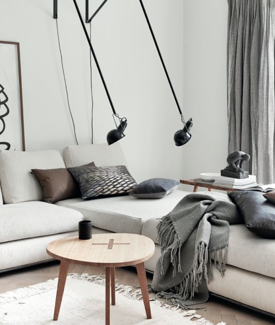 a neutral Scandinavian living room with touches of black for drama and cozy blankets and pillows