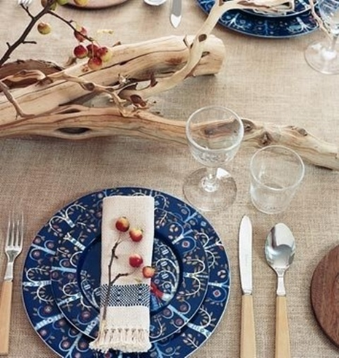 a fall Scandinavian tablescape with a burlap tablecloth, some driftwood with tiny apples and patterned plates