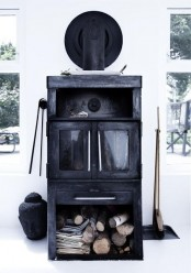 a black shabby chic fireplace with a firewood storage space makes a statement in this white space
