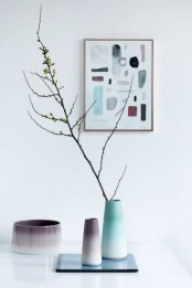 a fall Nordic centerpiece of a mirror and ombre vases in purple and turquoise plus branches for a Nordic feel
