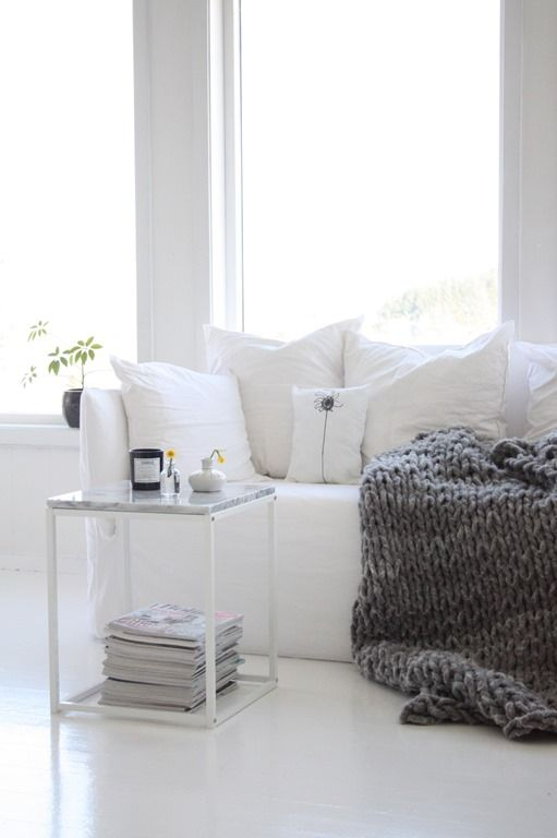 a cozy white nook spruced up with a heavy knit blanket for the fall is a great Nordic inspired idea