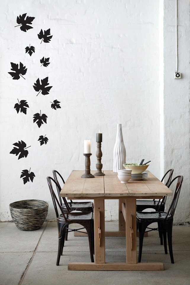 a Nordic dining space with white brick walls, black leaves and a dining table with mismatching chairs