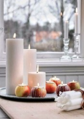 a fall Nordic centerpiece of a tray with pillar candles and apples with candles isnerted inside is a very easy decoration