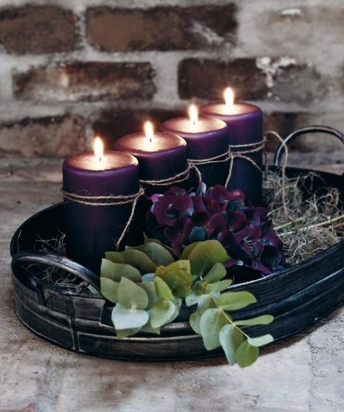 a fall Scandinavian centerpiece of a dark metal tray, purple candles, hay and purple hydrangeas and eucalyptus
