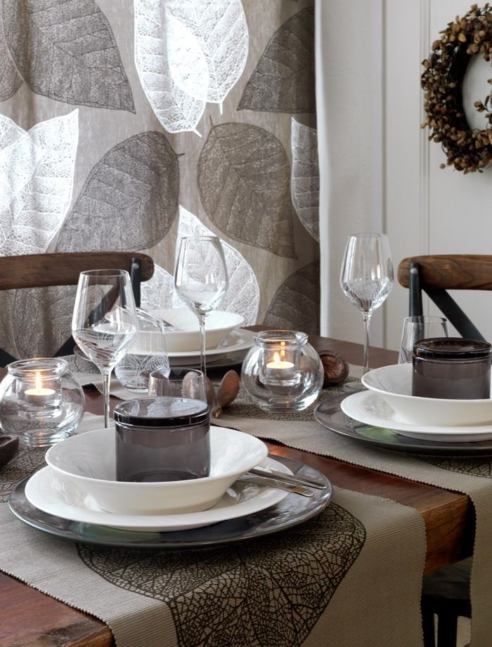 a Nordic fall tablescape made in greys, with a leafy curtain, candles, a wreath and some greyish textiles
